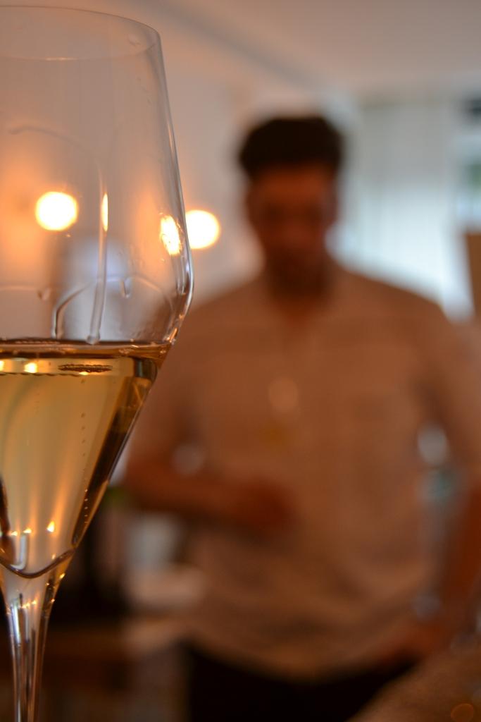 Champagnerglas im vordergrund mit Stefan im Hintergrund