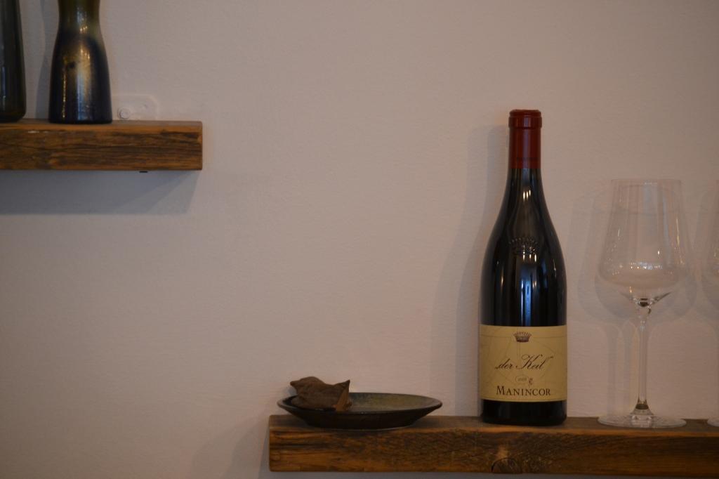 Detailfoto: 2 regale mit Rotwein und Vasen